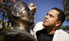 O professor Felipe Botelho Corrêa tira o pó do busto de Lima Barreto: pesquisa foi feita durante seu doutorado na Inglaterra Foto: Fernando Lemos