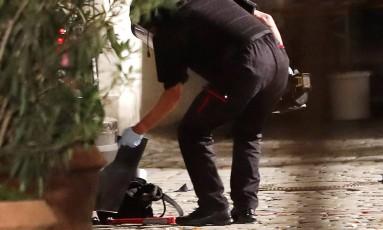 Policial analisa mochila deixada em frente a prédio em Ansbach, onde um homem se explodiu perto de festival de música Foto: Matthias Schrader / AP