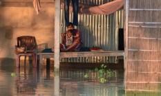 Uma mulher indiana brinca com seu filho na aldeia Sildubi, no distrito de Morigoan, afetada pelas inundações Foto: BIJU BORO / AFP