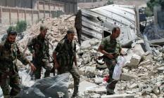 Forças do regime sírio caminham entre destroços em Aleppo Foto: SANA / REUTERS