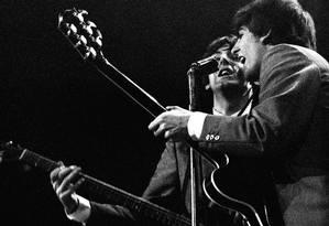Paul McCartney e John Lennon dividem o microfone na primeira turnê americana dos Beatles, em 1964 Foto: Mike Mitchell / Agência O Globo