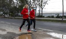Atletas do Cazaquistão passam por buracos na rua em frente à Vila dos Atletas Foto: Alexandre Cassiano / Agência O Globo