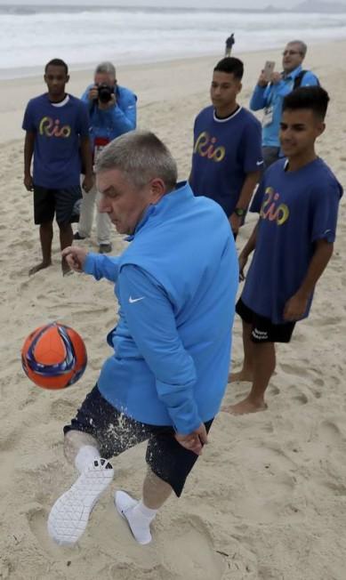 À tarde, bate bola com alunos de uma escola de futebol, na praia da Barra Charlie Riedel / AP