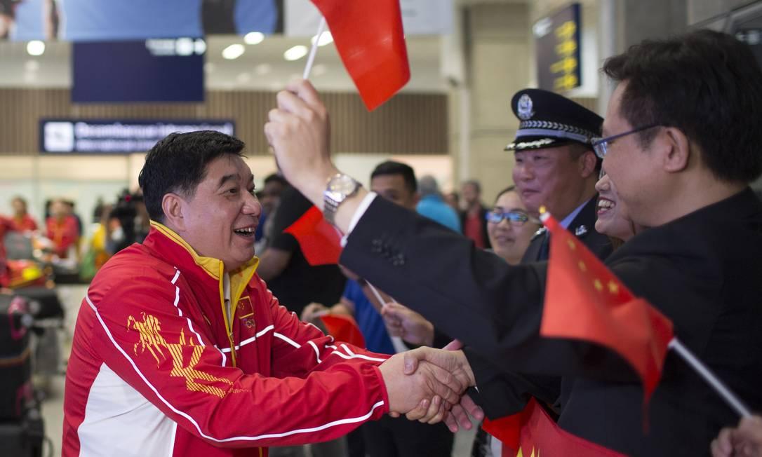 O treinador da equipe chinesa de tiro esportivo, Wang Yifu, é cumprimentado ao desembarcar no Aeroporto Internacional do Rio de Janeiro Leo Correa / AP