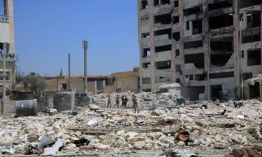 Forças leais ao presidente da Síria, Bashar al-Assad, caminham por edifícios destruídos na cidade de Aleppo Foto: SANA / REUTERS