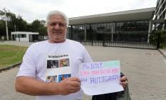 Luiz Alberto com um cartaz em que pede o autógrafo de Usain Bolt Foto: Guilherme Pinto/Extra