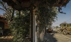 Máquinas diante da casa de Anderson de Souza, na Avenida Raul de Oliveira Rodrigues: seis metros do terreno, a partir do muro, serão desapropriados para a ampliação da via, trecho da Transoceânica Foto: Guilherme Leporace / Agência O Globo
