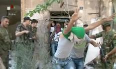 """Imagem da TV estatal síria mostra o que seriam jovens rebeldes se rendendo às tropas do governo em Aleppo, onde dezenas de famílias civis estariam deixando os sitiados bairros dominados pelos insurgentes por meio de """"corredores humanitários"""" Foto: Uncredited / AP"""