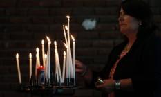 Mulher presta homenagem em igreja em Saint-Etienne-du-Rouvray, na França Foto: CHARLY TRIBALLEAU / AFP