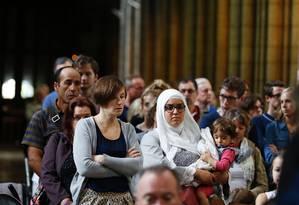 Uma mulher muçulmana com uma criança durante missa em tributo ao padre assassinado, na Catedral Rouen Foto: CHARLY TRIBALLEAU / AFP