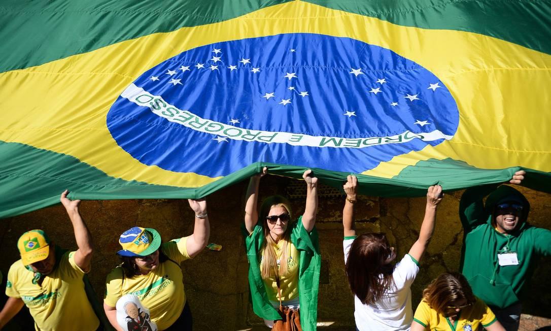 Manifestantes carregam uma grande bandeira do Brasil durante o ato ANDRESSA ANHOLETE / AFP