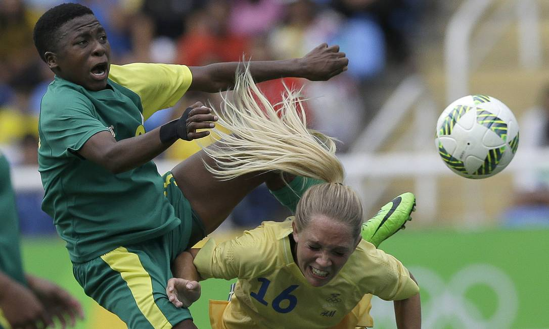 O jogo teve disputas duras pela bola, como essa entre a sul-africana Nothando Vilakazi e a sueca Elin Rubensson Leo Correa / AP