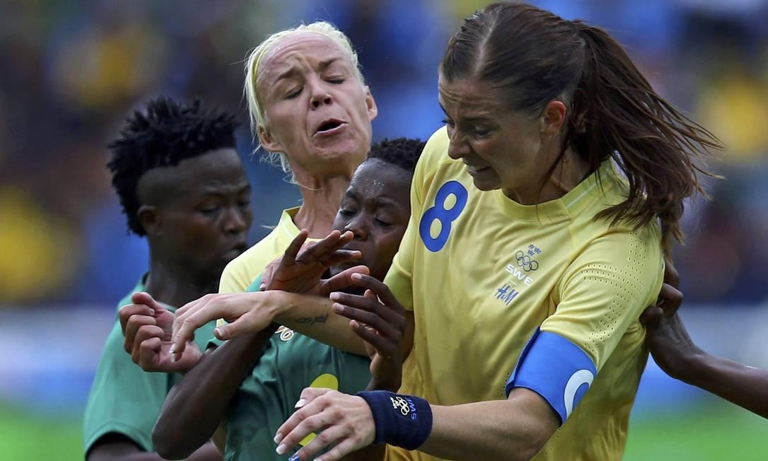 Na disputa de bola, Lebohang Ramalepe, da África do Sul, ficou imprensada entre as suecas Caroline Seger e Lotta Schelin LEONHARD FOEGER / REUTERS