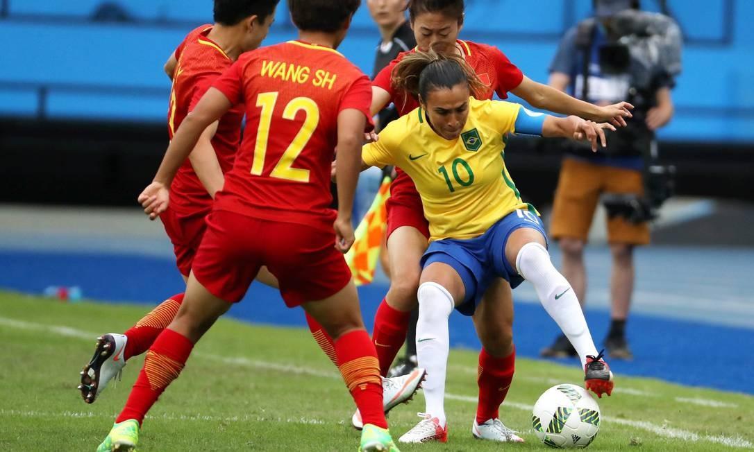 Marta cercada por três adversárias chinesas, no primeiro jogo da seleção brasileira nos Jogos do Rio Marcelo Carnaval / Agência O Globo