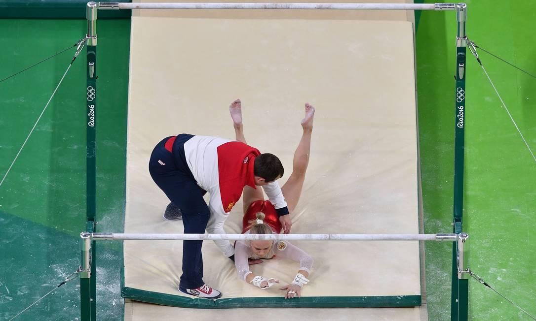 Ginasta russa é amparada por treinador após queda das barras paralelas durante sessão de treinos BEN STANSALL / AFP