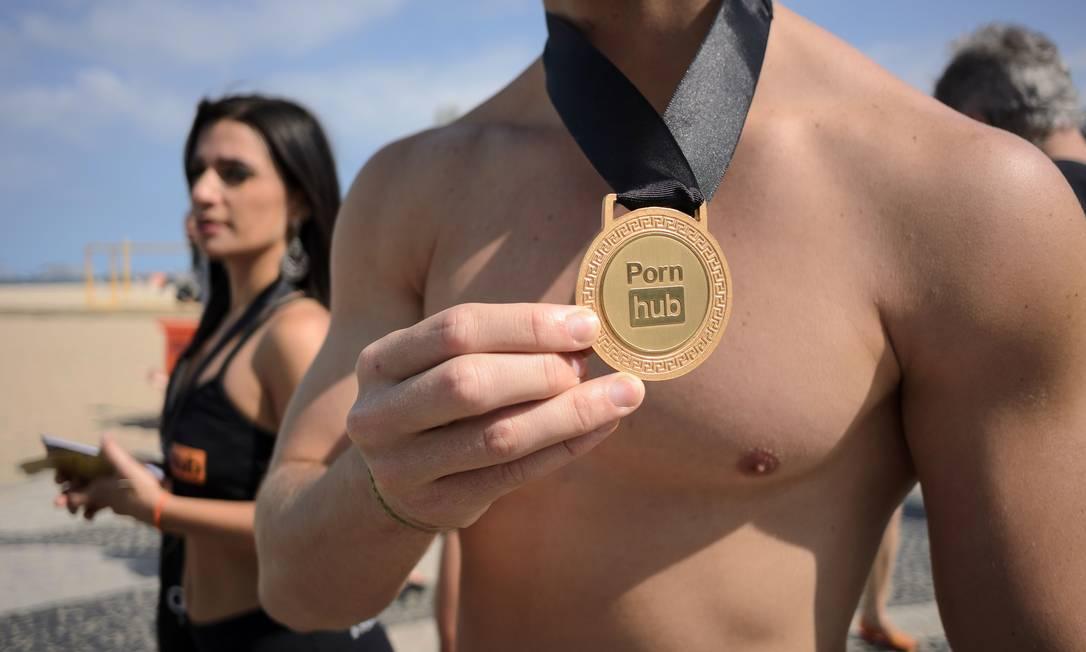 Casal aproveita a movimentação olímpica em Copacabana para divulgar o site 'caliente' LEON NEAL / AFP