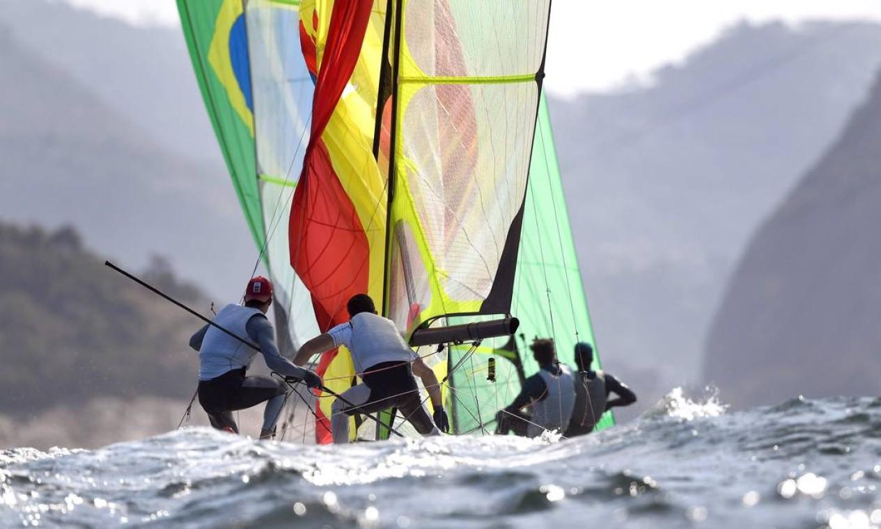Velejadores da Espanha e do Brasil, na raia olímpica da Baía de Guanabara Foto: WILLIAM WEST / AFP