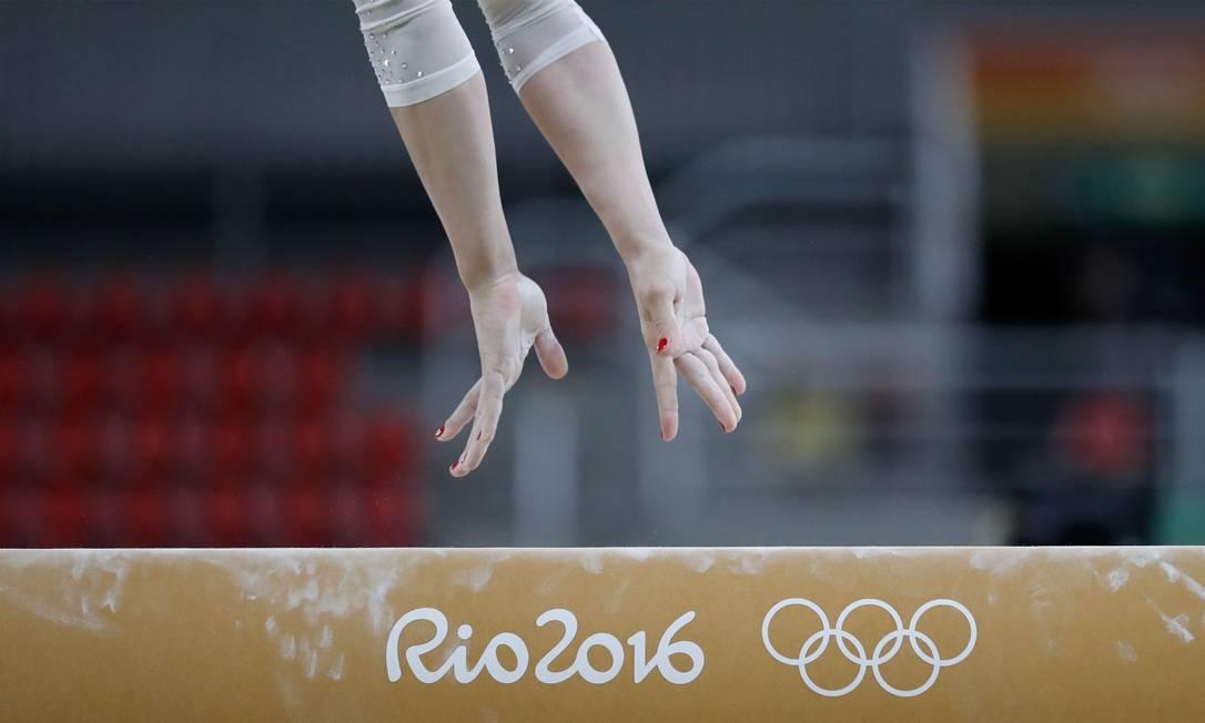 Ginasta treina na trave de equilíbrio na Arena Rio THOMAS COEX / AFP