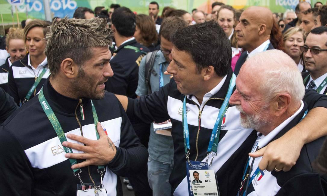 Primeiro ministro italiano, Matteo Renzi (ao centro) fala com atletas da delegação de seu país na Vila Olímpica JIM WATSON / AFP