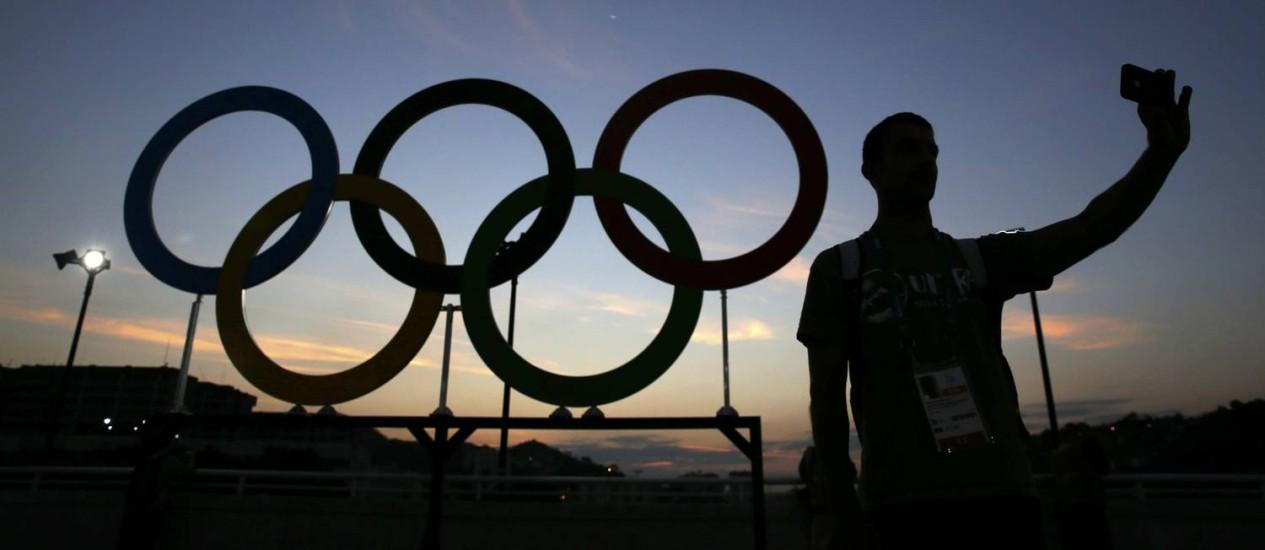 Homem posa para selfie em frente aos anéis olímpicos perto do Maracanã Foto: ADREES LATIF / REUTERS