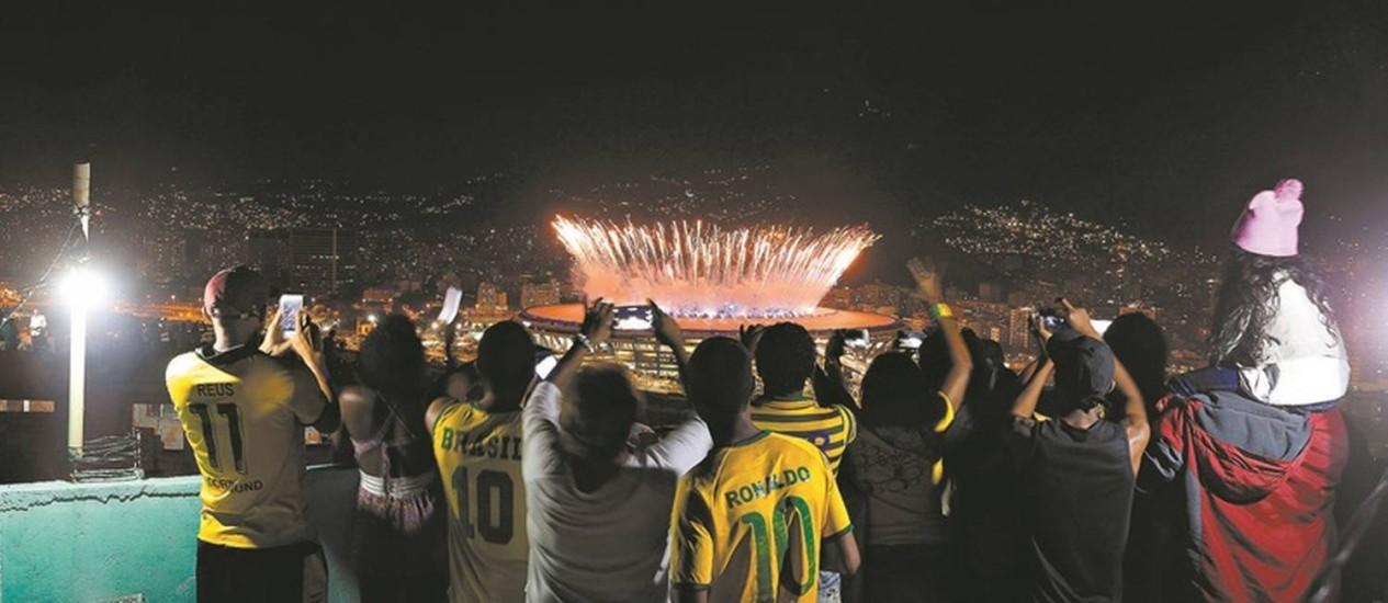Numa laje no alto do Morro da Mangueira, uma família acompanha a cerimônia de abertura da Olimpíada do Rio Foto: Domingos Peixoto / Agência O Globo