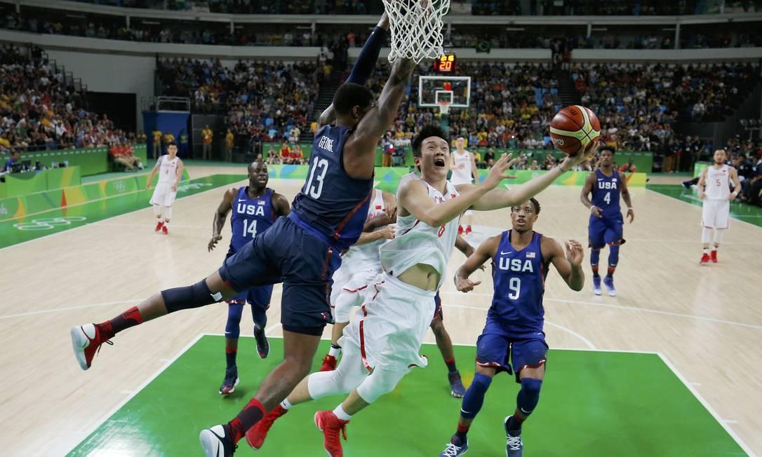 O jogador chinês, Ding Yanyuhang, passa pelo americano Paul George e marca dois pontos para a China JIM YOUNG / REUTERS