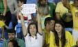 Torcedora segura cartaz 'Fora Temer' durante jogo do futebol feminino entre Brasil e Suécia