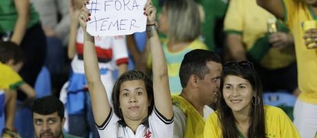 Torcedora segura cartaz 'Fora Temer' durante jogo do futebol feminino entre Brasil e Suécia Foto: Leo Correa / AP