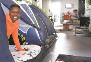 """A americana Terri Pollard, que trabalha como voluntária nas competições de hóquei, no seu cantinho no Rio: uma barraca de camping dentro de uma """"casa galpão"""