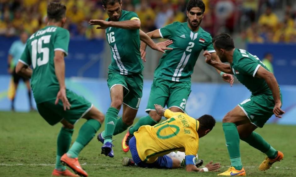 Neymar cai, cercado por quatro jogadores do Iraque Foto: Eraldo Peres / AP