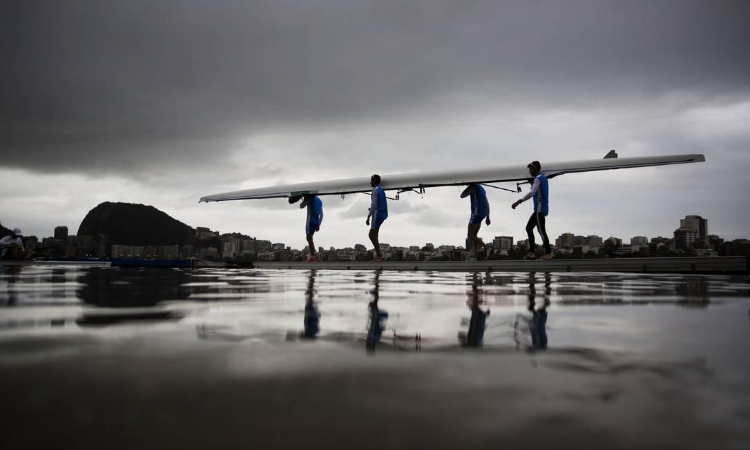 A equipe de remo da Itália carrega seu barco para um cais estádio da Lagoa David Goldman / AP