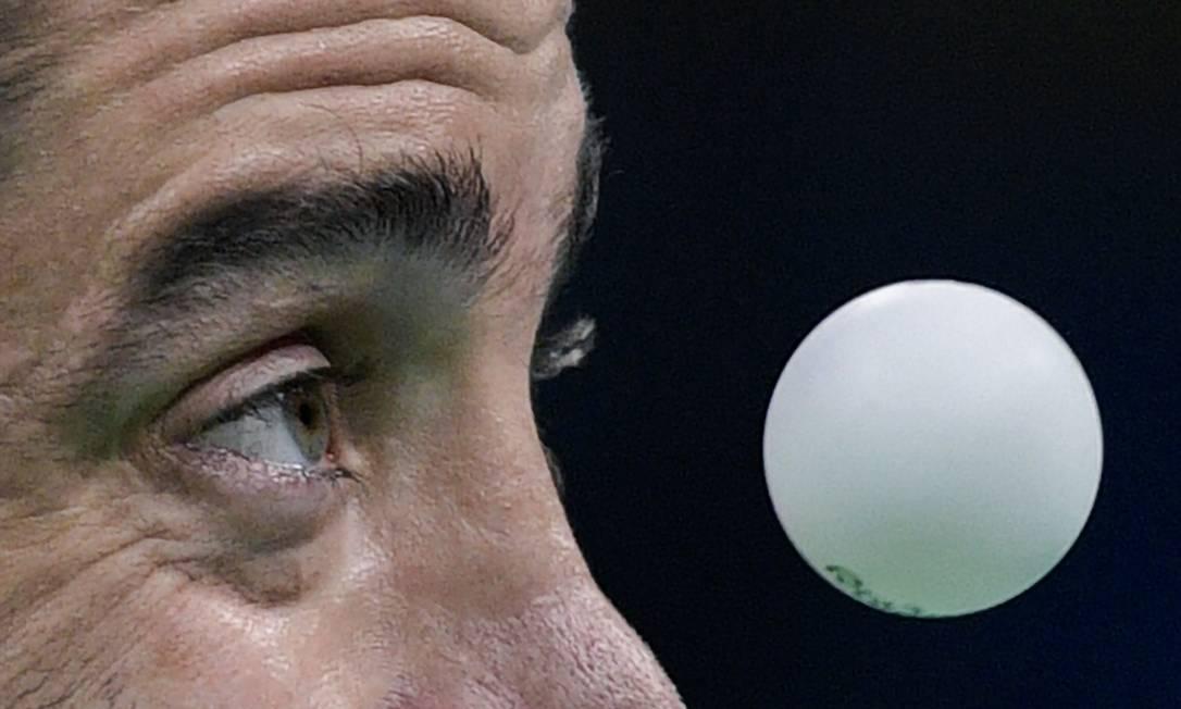 O grego Panagiotis Gionis de olho na bola durante a qualificação do tênis de mesa JUAN MABROMATA / AFP