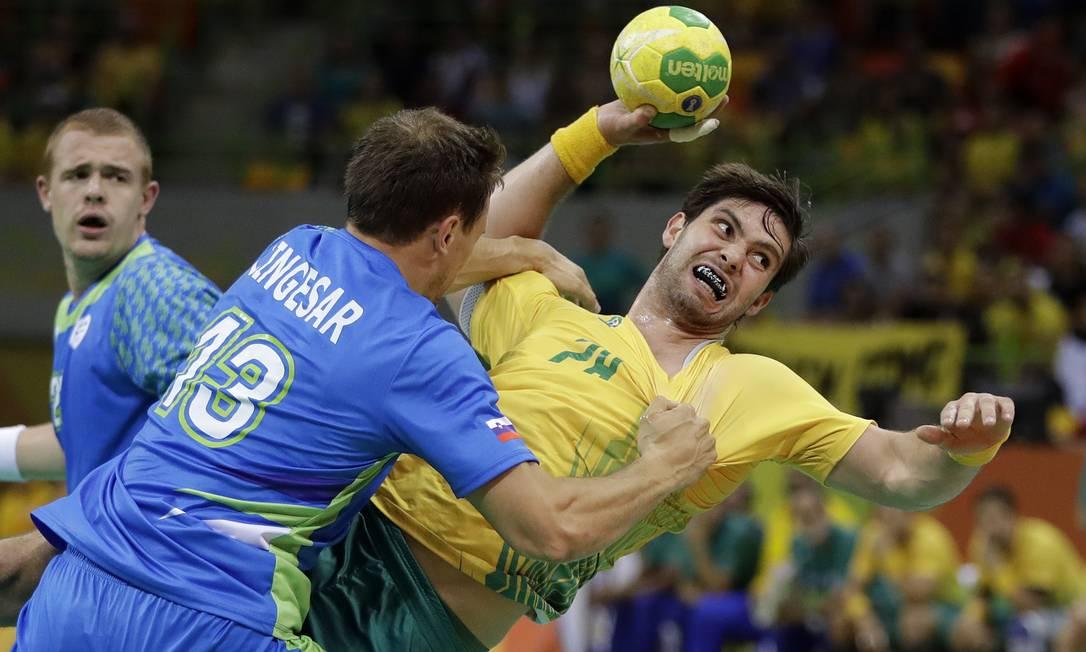 O jogador brasileiro, Leonardo Santos, tenta passar pela marcação do esloveno Darko Cingesar Matthias Schrader / AP