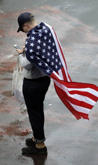 O torcedor Norte Americano aproveitou a bandeira para se proteger da chuva Eduardo Verdugo / AP
