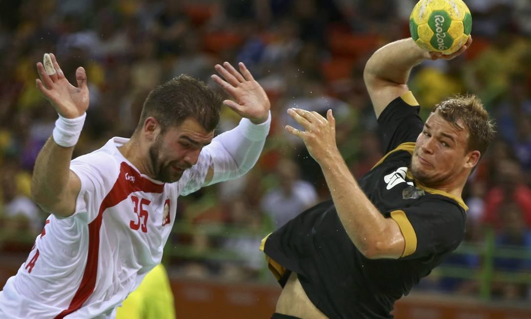 Mateusz Kus (Polônia) e Paul Drux (Alemanha) disputam um lance no handebol MARKO DJURICA / REUTERS