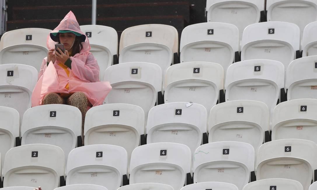 A chuva não atrapalhou a torcedora de registrar a partida do vôlei de praia Jorge William / Agência O Globo