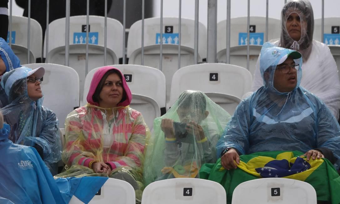 Mesmo protegido da chuva, garoto prefere jogar no tablet ao acompanhar a partida na Arena de Vôlei de Praia Jorge William / Agência O Globo