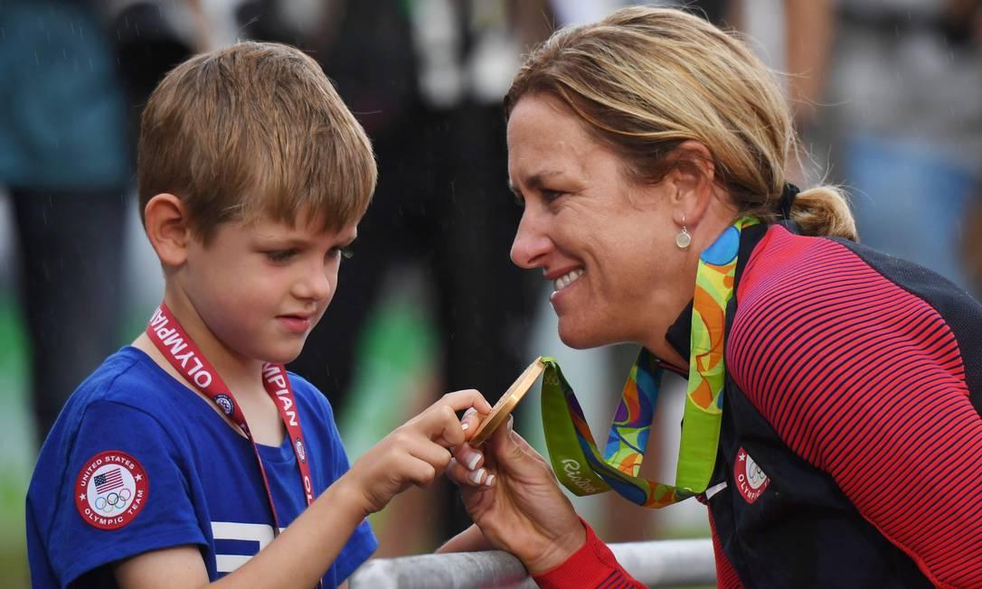 Kristin Armstrong mostra ao filho a medalha de ouro que ganhou na Olimpíada ERIC FEFERBERG / AFP