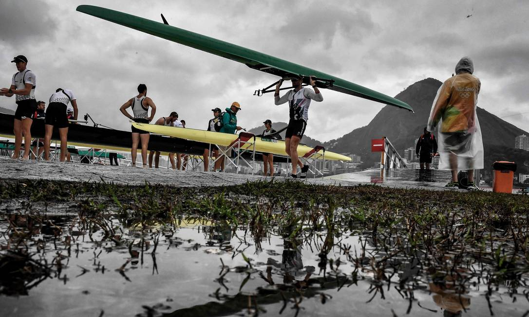 Atletas carregam seus barcos depois ddo cancelamento das provas de remo dessa quarta-feira, devido ao mau tempo JEFF PACHOUD / AFP