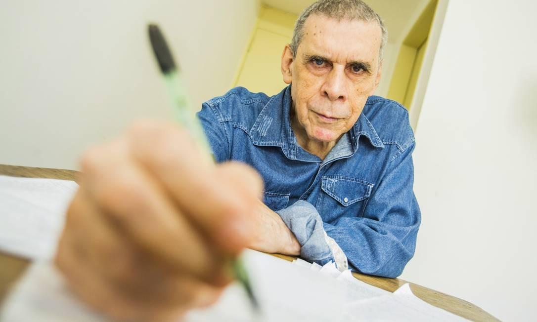 O escritor em seu apartamento em Laranjeiras: contos iniciam-se a partir de rabiscos em caneta sobre folhas de papel Foto: Bárbara Lopes / Agência O Globo