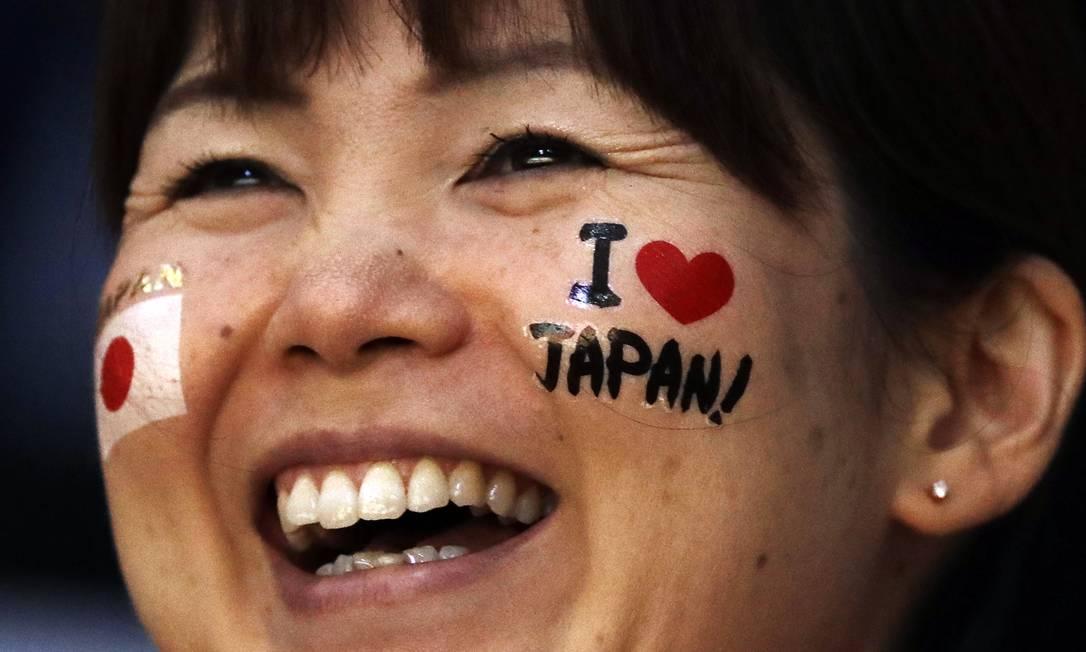 Torcedora japonesa sorri enquanto vê o jogo de voleibol entre China e Porto Rico Matt Rourke / AP