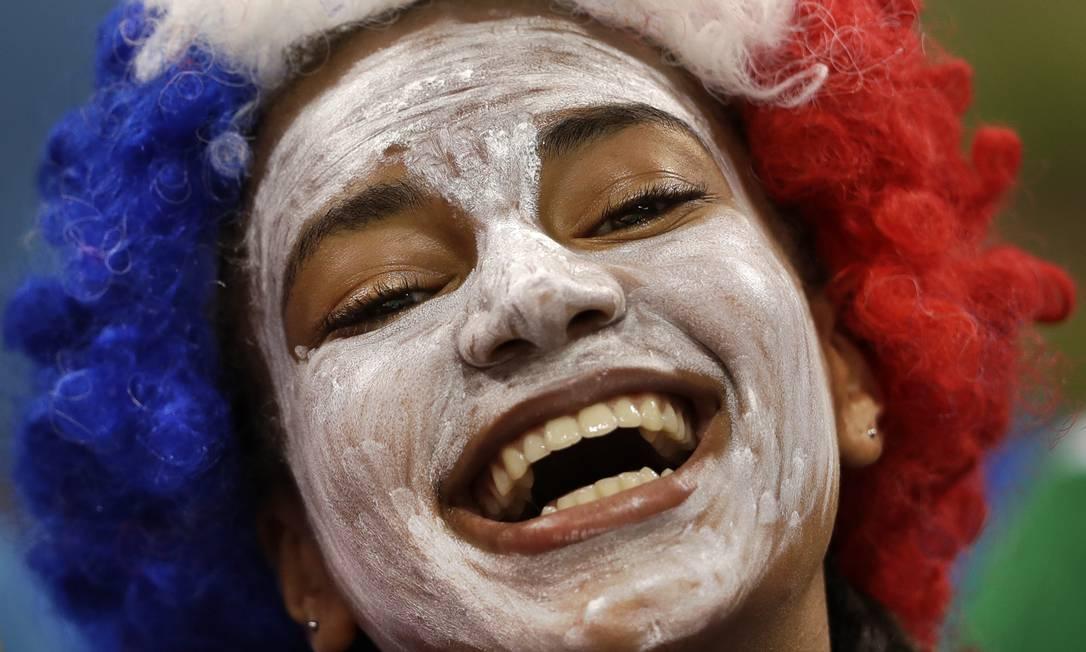 Torcedora francesa sorri antes da partida de handebol feminina entre França e Rússia Ben Curtis / AP