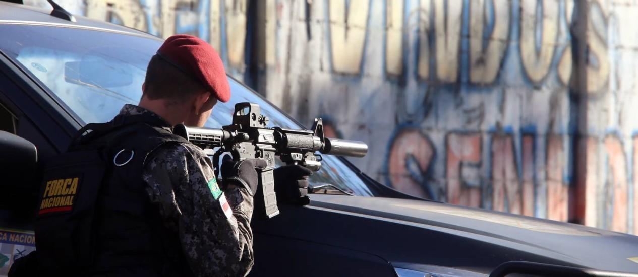 Militar da Força Nacional em operação para prender os acusados de atirar no veículo que entrou por engano na Vila do João Foto: Fabiano Rocha em 11/08 / Agência O Globo