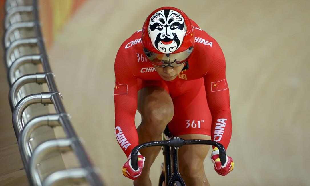 O cilcista Xu Chao em ação: a máscara chinesa desenha no capacete dá um efeito interessante quando o atleta abaixa a cabeça para ganhar mais aerodinâmica PAUL HANNA / REUTERS