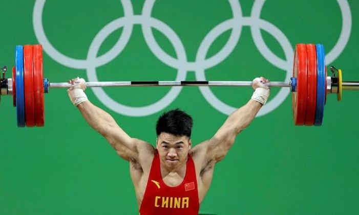 O atleta chinês estabeleceu o novo recorde mundial de arremesso na categoria até 85 quilos. Na modalidade, o atleta sustenta a barra com as anilhas em duas fases: primeiro, tira a carga do chão e, depois, precisa levantá-la sobre a cabeça, o que fez com 217 quilos. Foto: Divulgação / COI