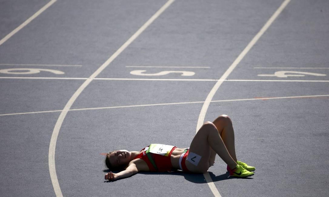 Atleta Anastasiya Puzakova, da Bielorrússia, deita na pista após a corrida. Na classificação geral, ela terminou na 50ª posição DAVID GRAY / REUTERS