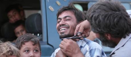 Homem raspa a barba de um civil em Manbij, no Norte da Síria Foto: RODI SAID / REUTERS