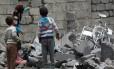 Crianças andam sobre os restos de uma casa destruída na capital do Iêmen, dominada por rebeldes hutis desde setembro de 2014