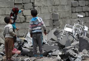 Crianças andam sobre os restos de uma casa destruída na capital do Iêmen, dominada por rebeldes hutis desde setembro de 2014 Foto: MOHAMMED HUWAIS / AFP