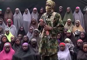 Vídeo mostra homem armado com o rosto coberto e dezenas de jovens mulheres, que seriam as estudantes sequestradas há dois anos em Chibok Foto: HO / AFP